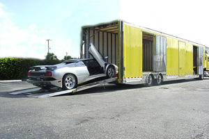 Car being loaded onto an enclosed carrier